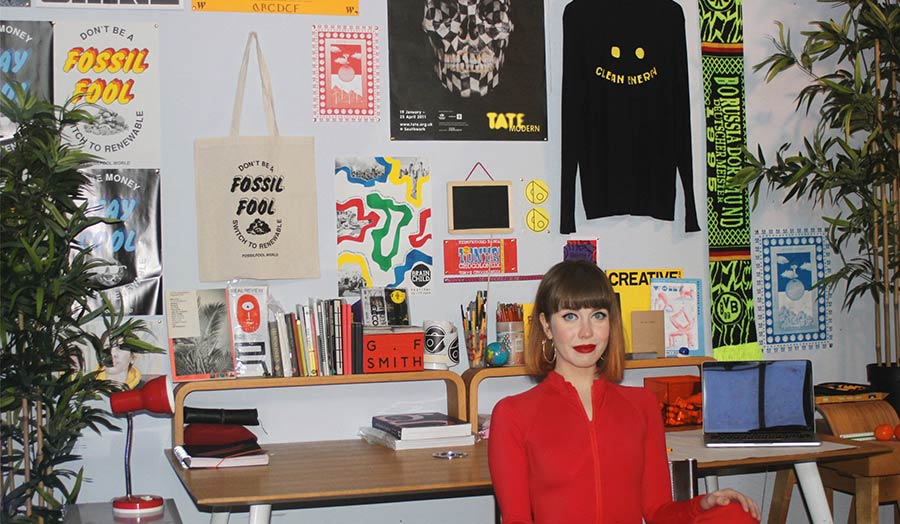 Portrait of the artist seated next to a display of her graphic design work