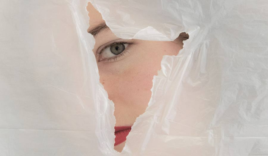 Half of a woman's face seen through a hole on a plastic sheet