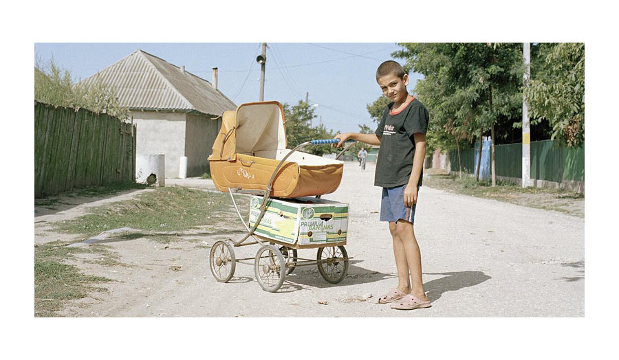 A boy with an antique pram on a rural street