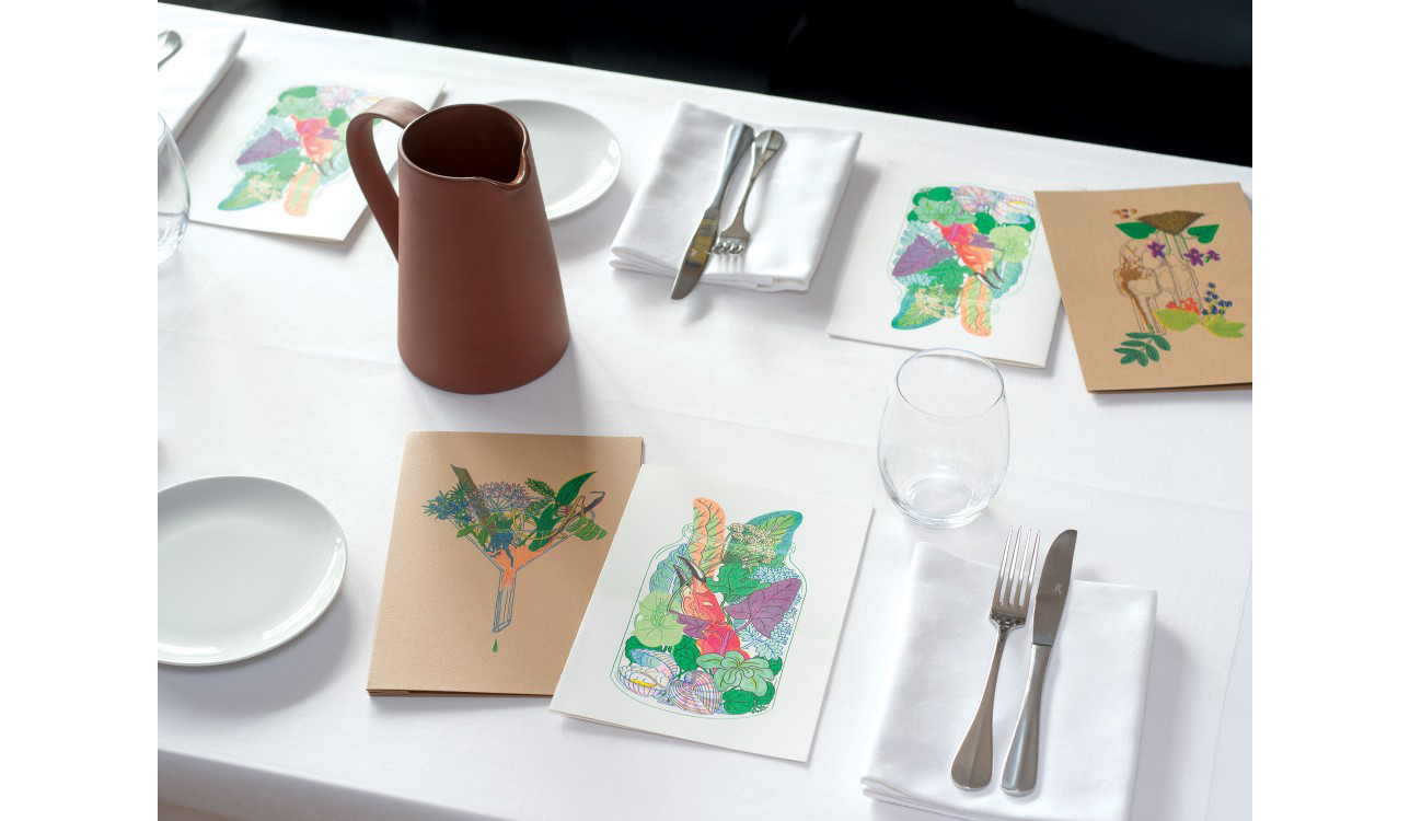 table with crockery and cutlery, and hand drawn menus