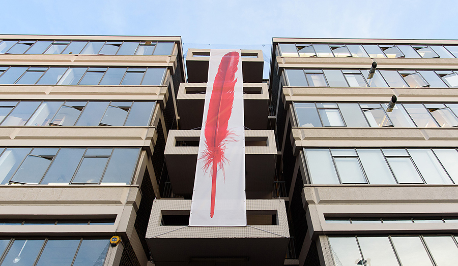 Photograph of a canvas with a red feather attached to the outside of The Cass building.