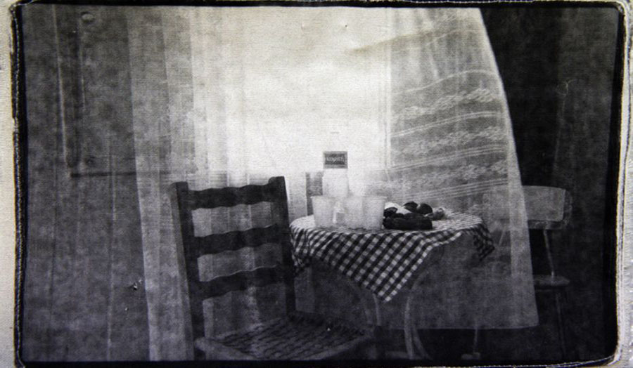 A photographic print showing a chair next to a table