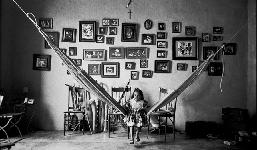 Black and white image of girl sitting in a room.