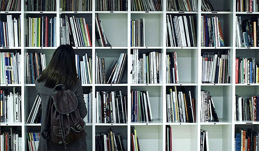 A student looking at a shelf of art and design books