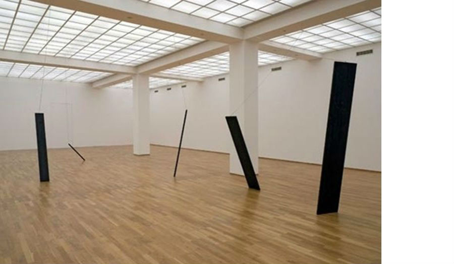 A gallery installation showing a series of rectangular materials at unusual angles