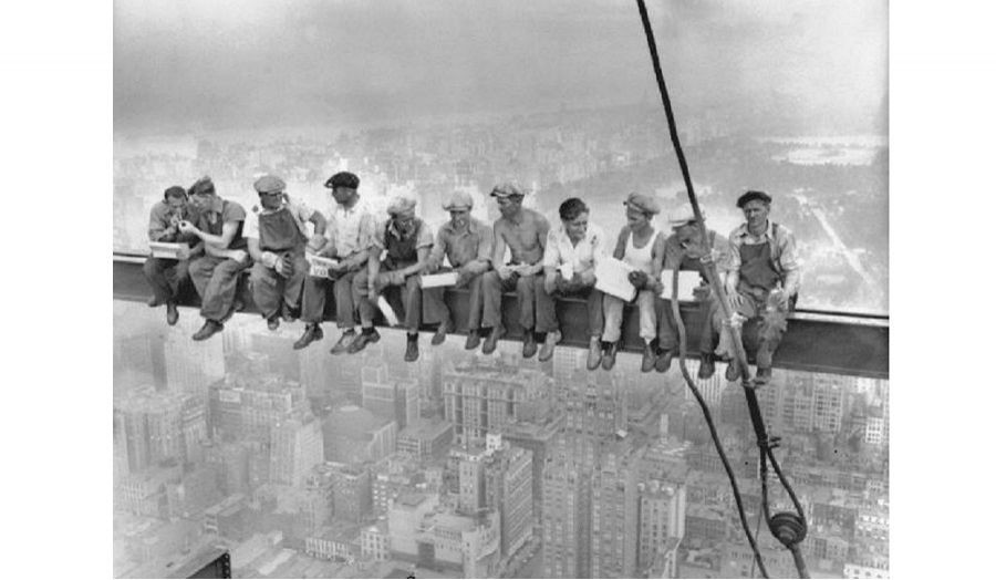 Old photo of workers taking a risky break sat on a crane high above a city