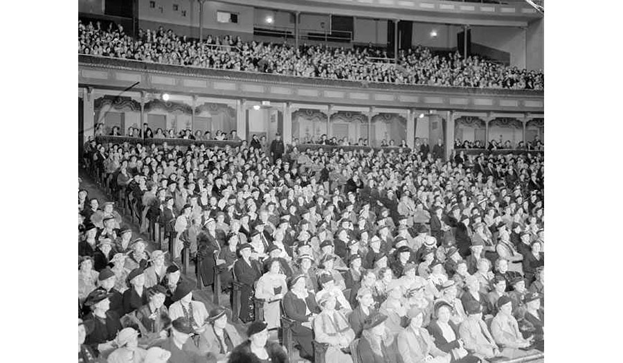 Black and white photograph of a crowd sitting in a theatre