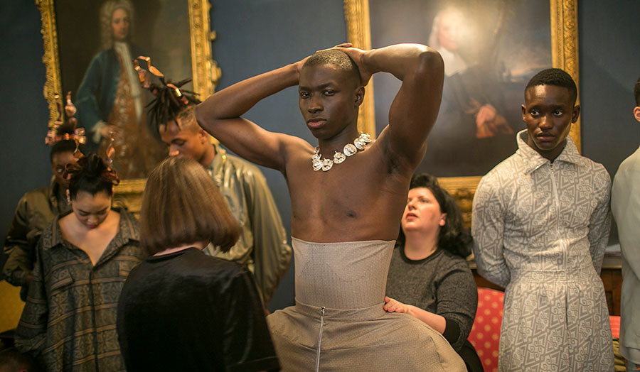 Male model being fitted with a corset in a gallery surrounded by historic paintings