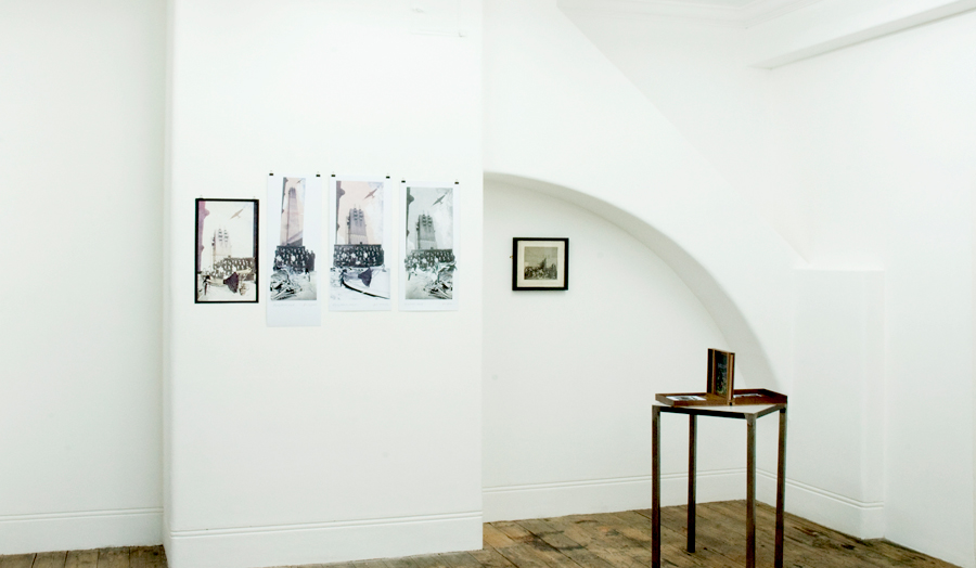 An exhibition space at Betts Gallery showing tall building artworks and table display