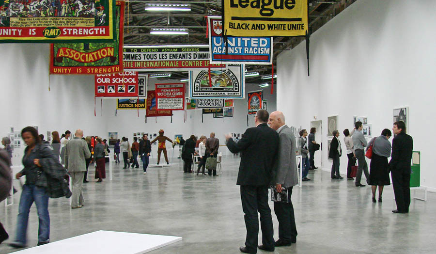 People in an exhibition space with revolutionary banners hanging from the ceiling