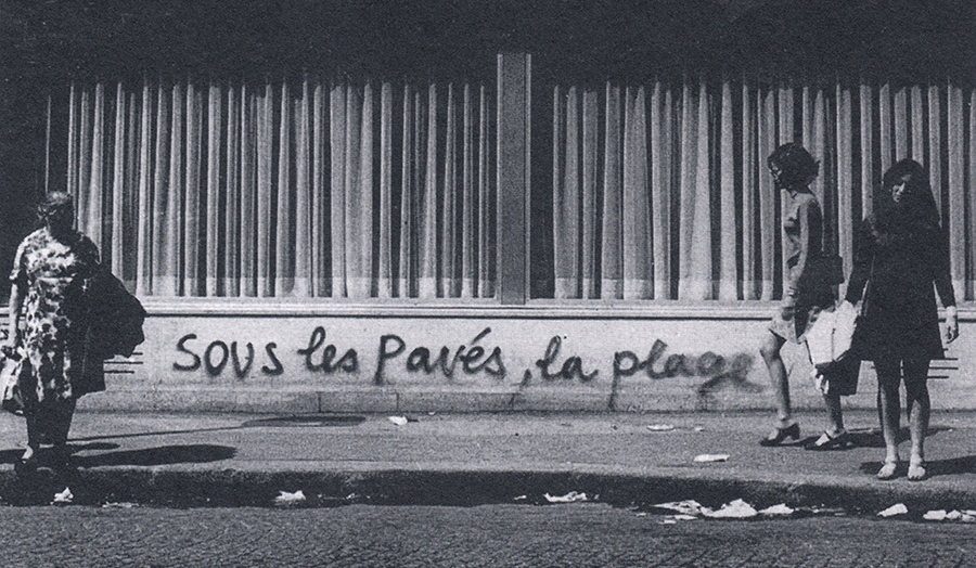 "Paris street with French graffiti slogan ""Sous les paves, la plage!"", as used by protestors"