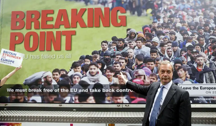 Farage pointing to his campaign poster