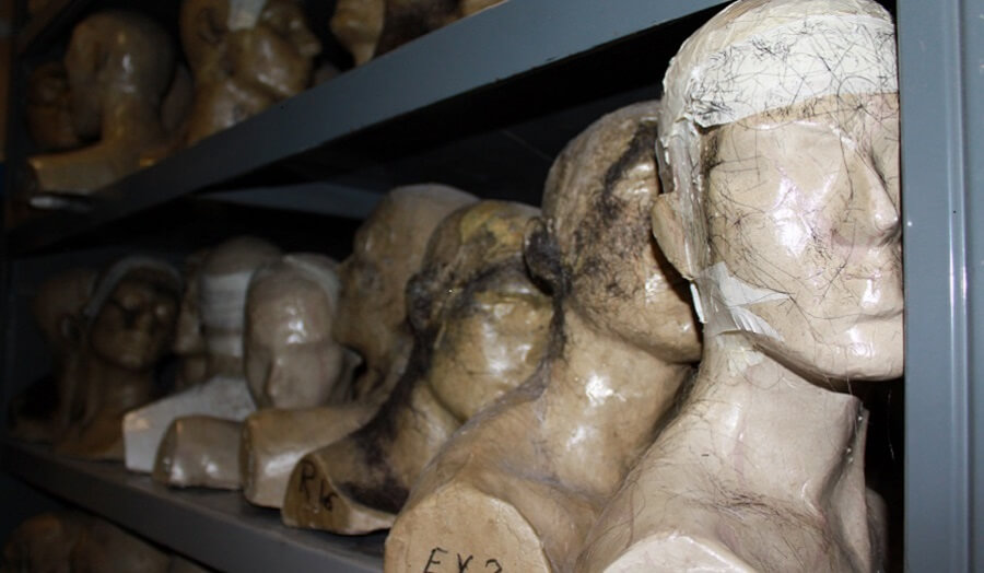 Many plaster cast heads on shelving within the studio