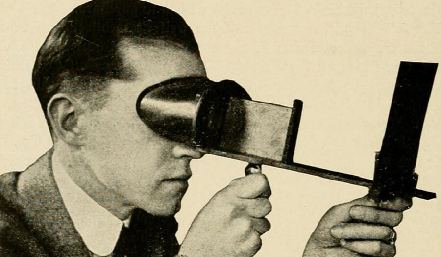 Victorian sepia photo of man's head looking through early 3D viewing device