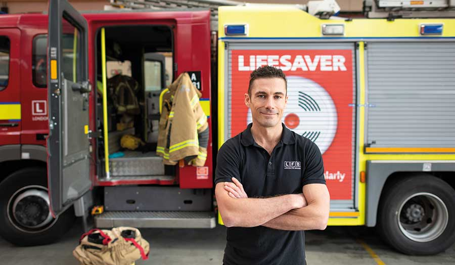 Greg Lessons, London Met alumnus, stands in front of a fire engine