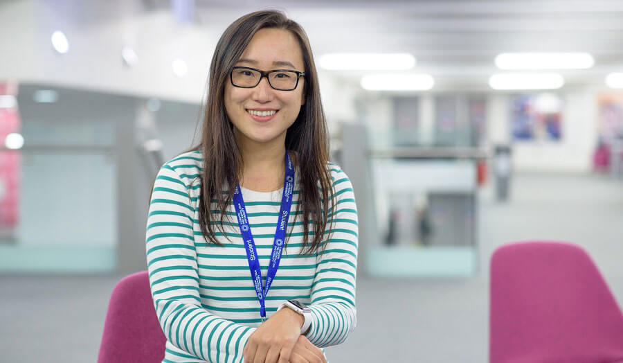 Smiling, bespectacled student Elly Zhang sits in the library.