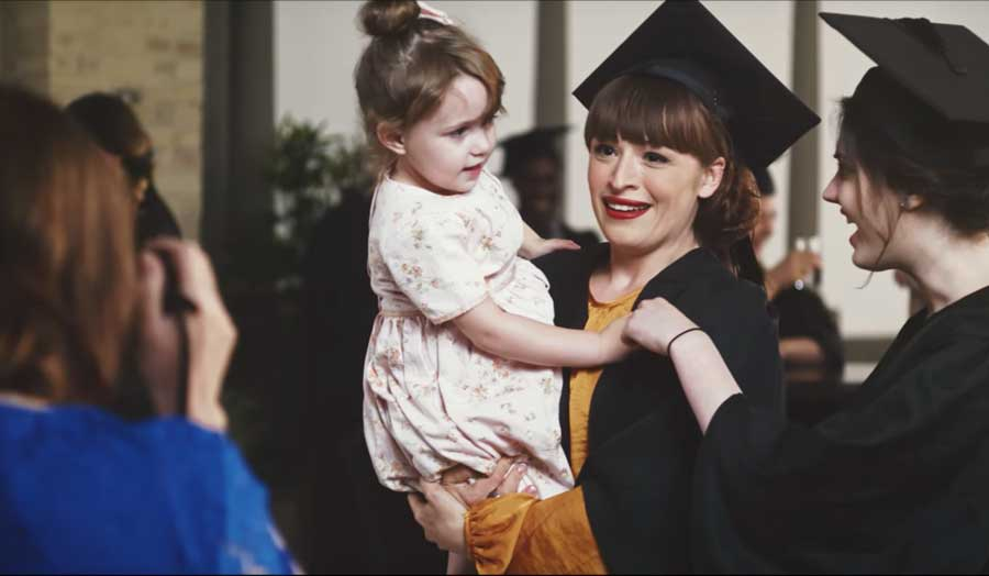 A student graduating holding her daughter