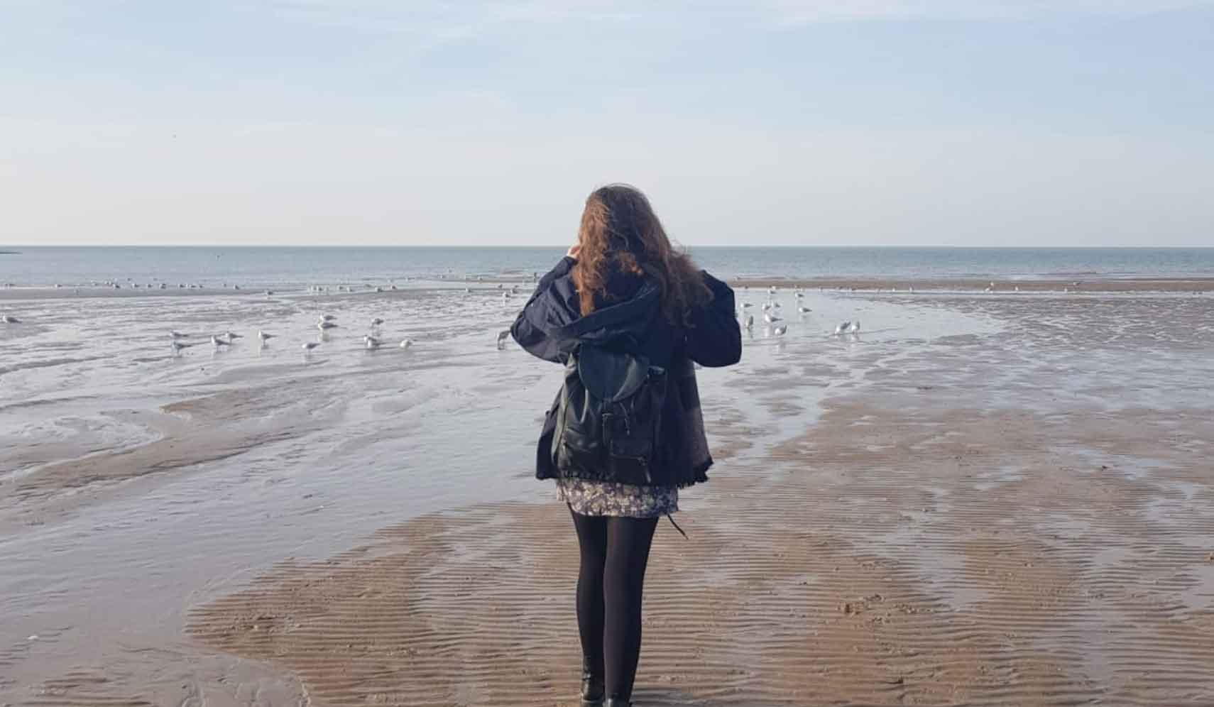 Student walking on a beach