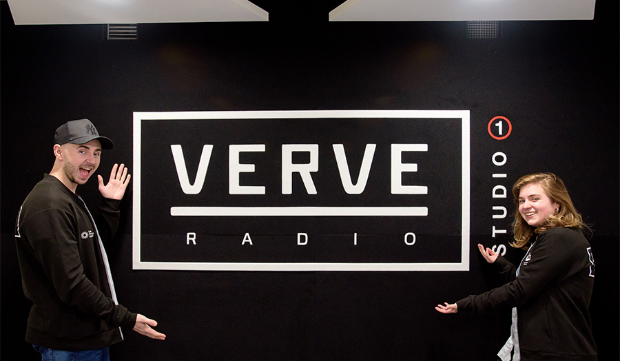 Shot of two people pointing at Verve sign