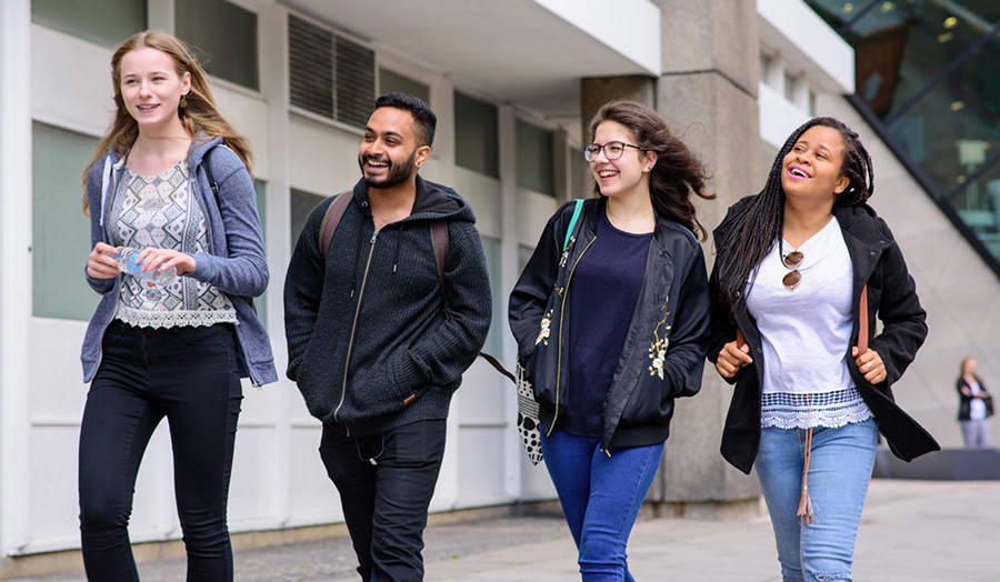 Photograph of four London Met students smiling and talking