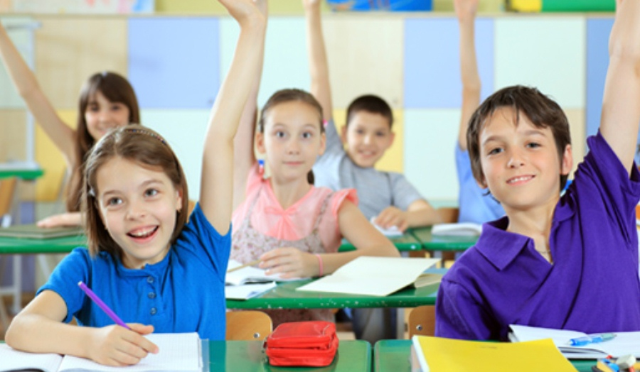 Primary school children in classroom wearing colorful clothes, hands up, smiling, bright colours