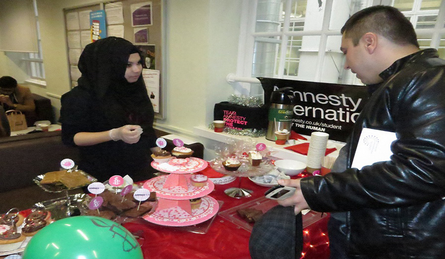 Students selling Valentine's Day themed cupcakes for Amnesty