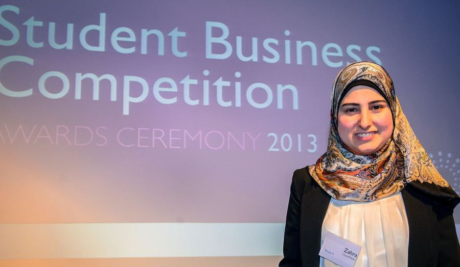 Zahra Charaffdeen winner of business competition poses before business competition screen