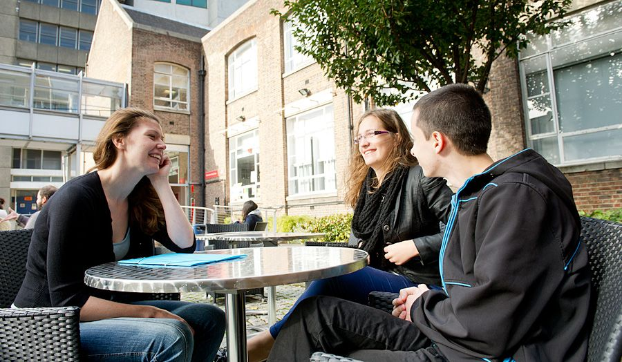 three students sat at a table outside in the courtyard at holloway talking and smiling