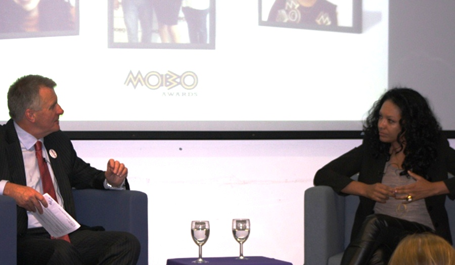 Peter McCaffery sitting opposite MOBO founder Kanya King on stage in the Henry Thomas Room