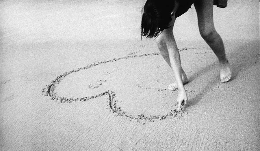 girl draws heart in sand on beach with finger