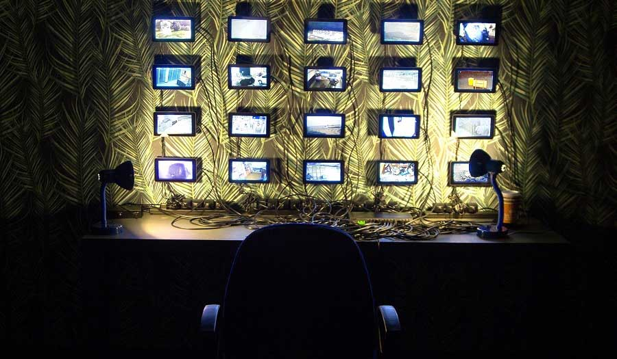 a bank of surveillance camera images on a wall in a dark room with an empty chair in front of them