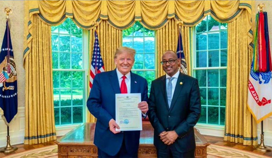 Ambassador Ali Sharif Ahmed standing next to President Donald Trump in the White House