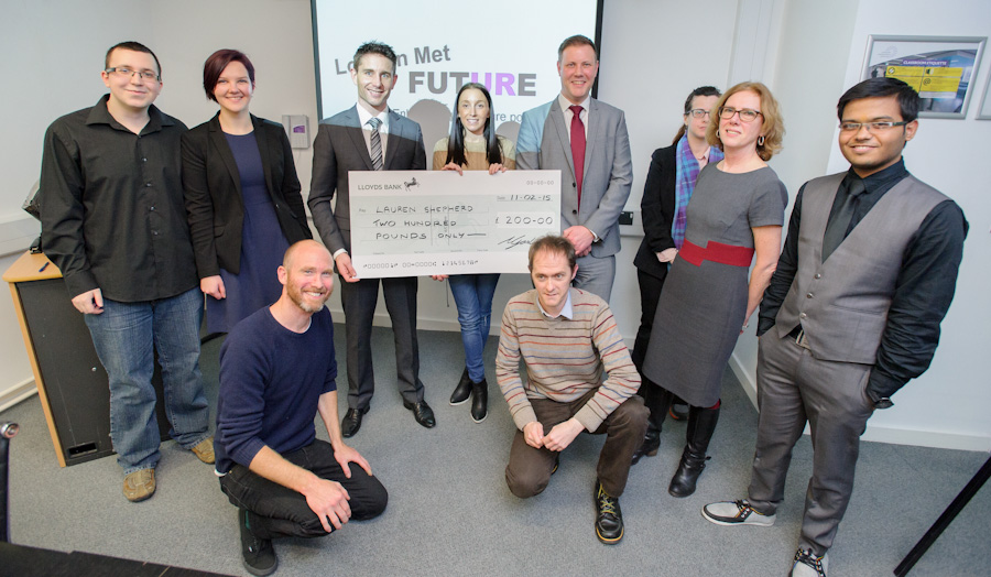 Student competition winner is presented with a large check surrounded by staff and event organisers