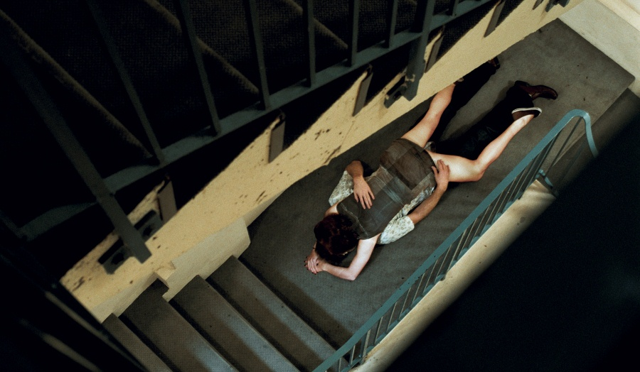 two people lying on top of each other in an empty concrete stairwell with green railings