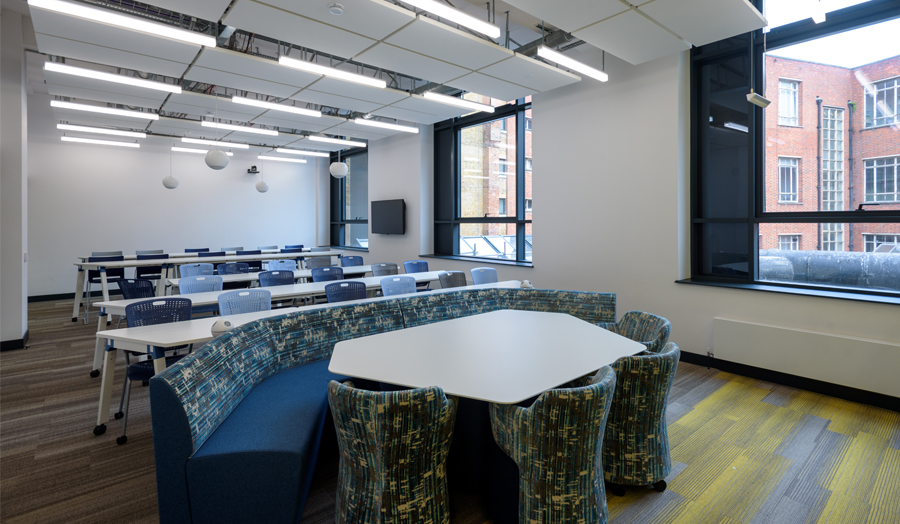 Roding Building first floor seminar room with rows of tables and huddle seating