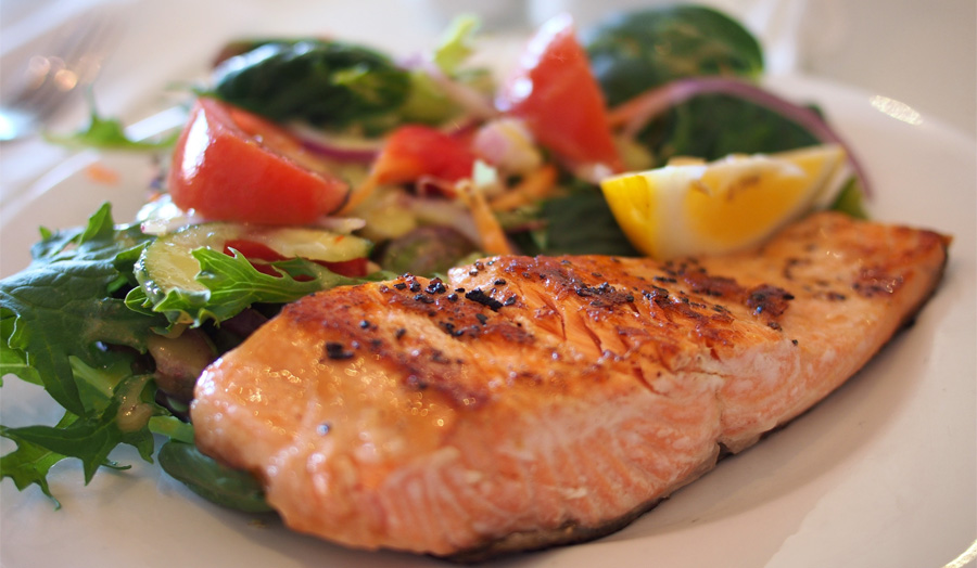 Plate with salmon fillet and salad leaves