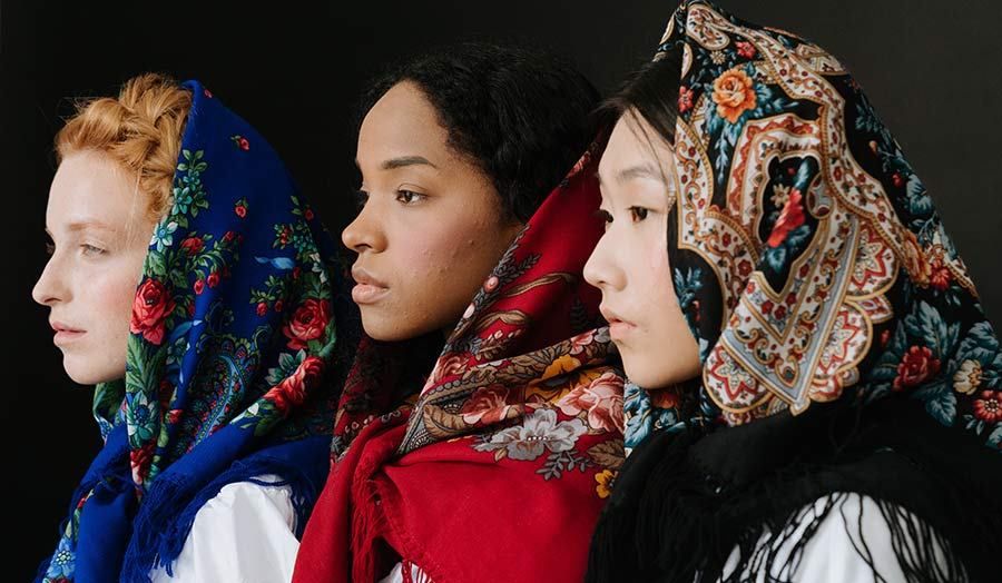 Three women of different cultural identities with a floral headscarf