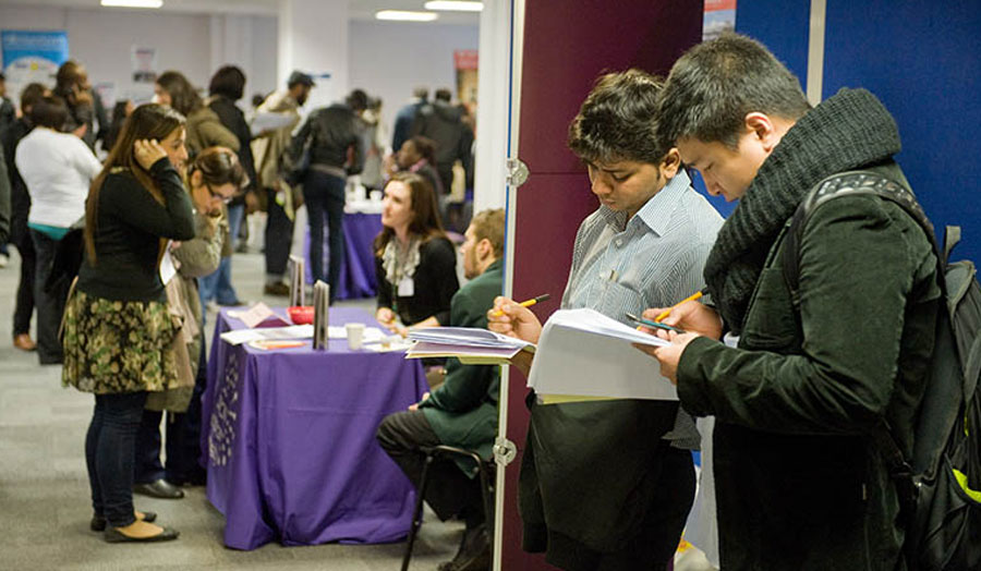 Two students writing down their notes at a career fair