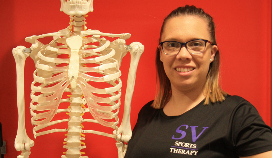 Nicole with a skeleton at SV Sports Therapy where she currently works