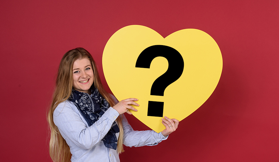 Student holding a heart with a question mark in it.
