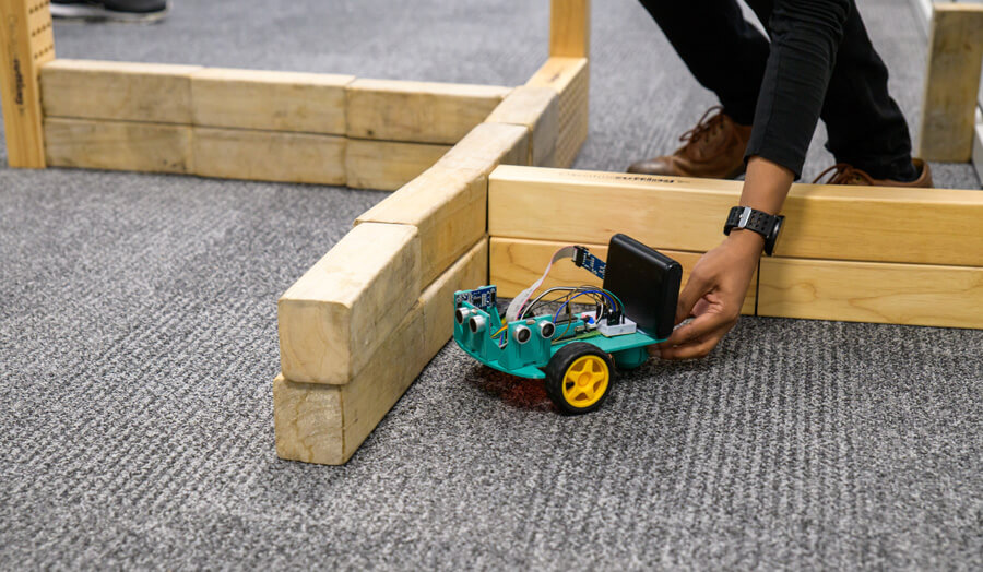 Student placing his robot in the test maze