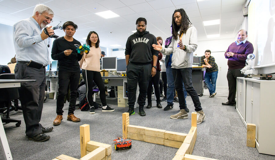 Students watching a robot navigate the maze 1