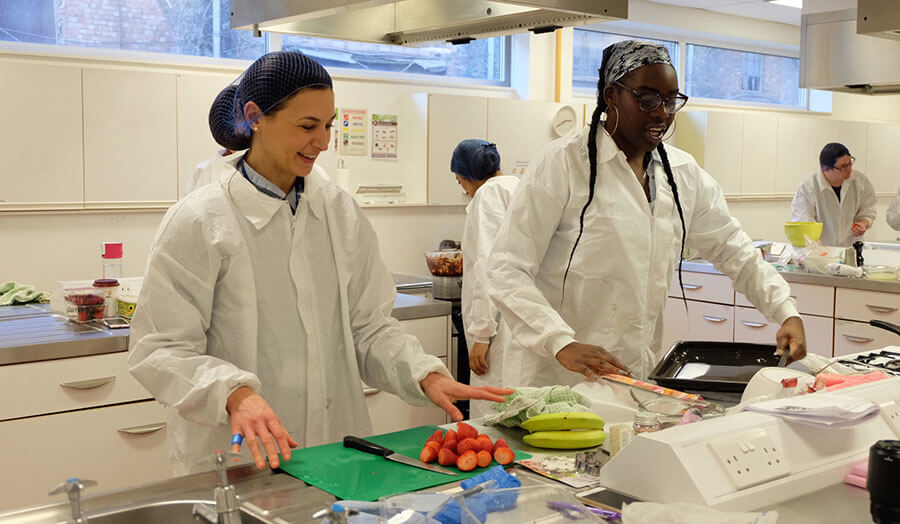 Two students chopping food in a London Met lab
