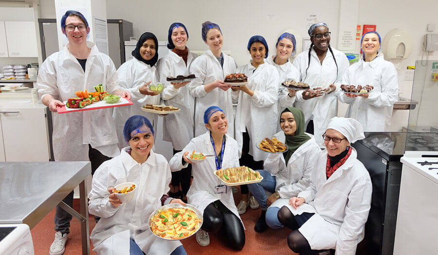 A group of students in their lab coats and hairnets happily hold finished food projects