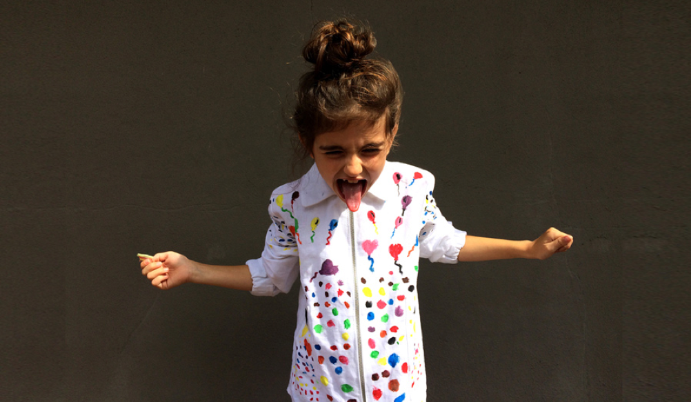 A child sticking her tongue out and wearing a colourful shirt